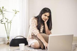 indisk ganska ung flicka som använder bärbar dator hemma foto