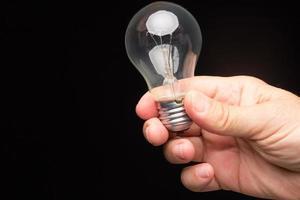 glödlampa i handen på en svart bakgrund foto