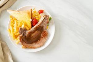 fläskkotlettbiff med chips och minisallad på den vita plattan foto