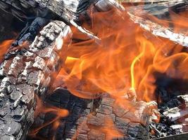 röd flamma från skivat trä, mörkgrå svart kol inuti metallpanna. foto