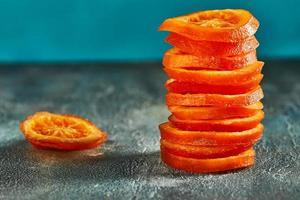 skivor av torkade apelsiner eller mandariner på en blå bakgrund foto