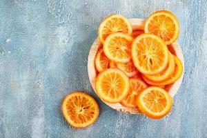 skivor torkade apelsiner eller mandariner i en träplatta foto