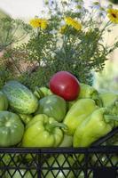 grönsaker i en svart låda och en armfull vildblommor. foto