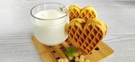 kakor hjärta, mjölk och vinbär bär. efterrätt på ett trä foto