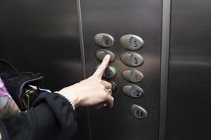 kvinna i en hiss som trycker på en knapp i rutan foto