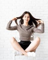 kvinna med långt hår som sitter på vit tegelväggbakgrund foto