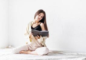 kvinna i bekväma hemmakläder som skriver anteckningar som sitter på golvet foto