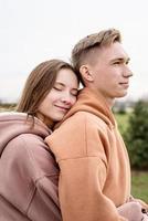 unga älskande par som omfamnar varandra utomhus i parken foto