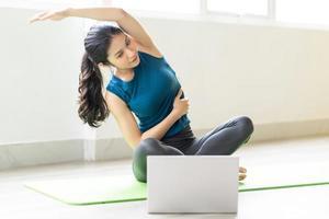 ung asiatisk tjej som gör övning på golvet ensam foto