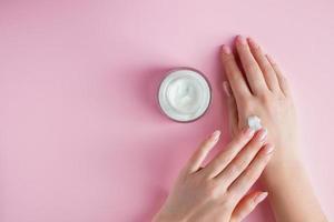 närande kräm och vackra kvinnliga händer på rosa bakgrund. foto