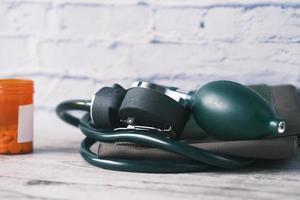 blodtrycksmaskin och medicinskt piller på bordet. foto