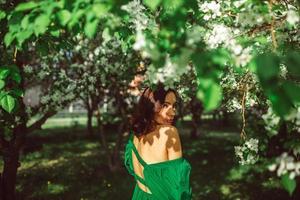 en ung flicka står i parken under ett blommande äppelträd foto