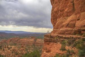 kvinna som står på en klippa bredvid röda stenar foto
