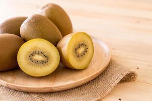 färsk gyllene kiwi i träplatta foto