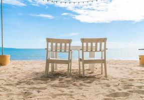 vita stolar och bord på stranden med utsikt över blått hav och klar himmel foto