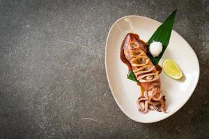 grillad bläckfisk med teriyakisås på tallriken foto