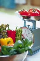 färska grönsaker på en skala foto
