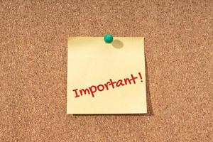 viktigt ord på gul anteckning på korkbräda foto