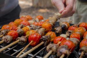 kycklinghjärtor med tomat- och lökmatlagning på varm grill foto