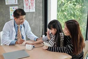 en mamma och dotter examen möte med en asiatisk manlig läkare. foto
