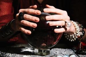 närbild av fortunetellers händer på en glaskula. mystisk interiör foto