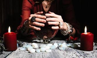 fortunetellers händer på en glaskula. mystisk interiör foto