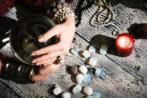 fortunetellers händer på en glaskula. mystisk interiör. ockulta symboler foto