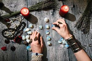 fortunetellers händer med sten runor, förutsägelse av framtiden. foto