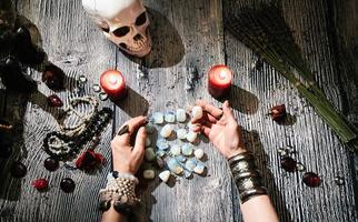fortunetellers händer med sten runor, ockulta symboler. foto