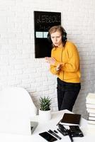 kvinna i hörlurar undervisning online med videochatt på bärbar dator foto