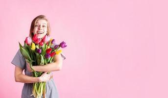 kvinna med bukett med färska tulpaner isolerad på rosa bakgrund foto