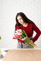kvinna blomsterhandlare som gör en bukett med färska färgglada tulpaner foto