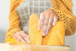 hand som håller hinkbröd färskt i brödbutik foto