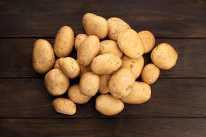 grupp nya potatisar på träbord. toppvy foto