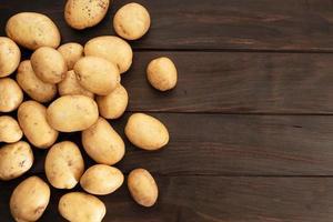 grupp nya potatisar på träbord. toppvy. kopiera utrymme foto