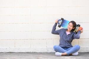 asiatisk kvinna med surfskatesammanträde mot betongväggen foto