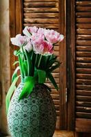 en mjuk fokuserad bukett blommor i en gammal vas foto