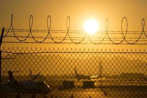 säkerhetsstaket runt den internationella flygplatsen vid soluppgång foto