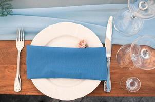 inställning av restaurangbord, blå servett, utomhus, dekoration av evenemang foto