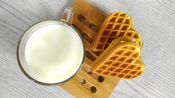kakor hjärta med en kopp med mjölk. hemlagade kakor för alla hjärtans dag foto