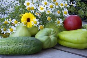 grönsaker och en bukett med vilda blommor närbild. Färska grönsaker foto