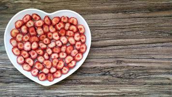 de skivade jordgubbarna är i en hjärtformad tallrik. romantisk servering foto