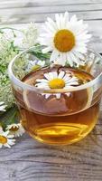 kamomill aromatiskt te i en glass kopp på en trä bakgrund. foto