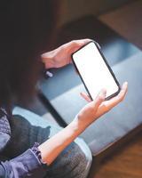 ung kvinna med smartphone med tom skärm mockup foto
