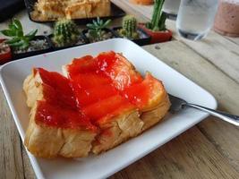 rostat bröd med smör och jordgubbssylt på träbakgrund foto