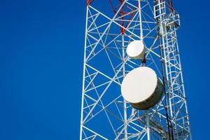närbild av ett telekommunikationstorn med blå klar himmel foto