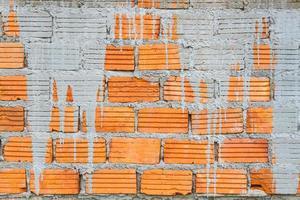 närbild orange horisontell texturerad tegelsten med torr betongfläck. foto