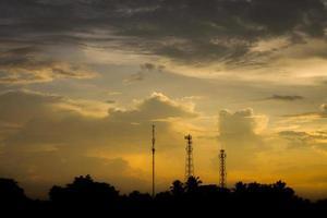 silhuettkommunikationsantenner i molnig himmel på kvällen foto