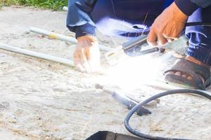 arbetare som svetsar stålet utan säkerhet foto