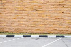 tom parkeringsplats med brun sandstenvägg foto